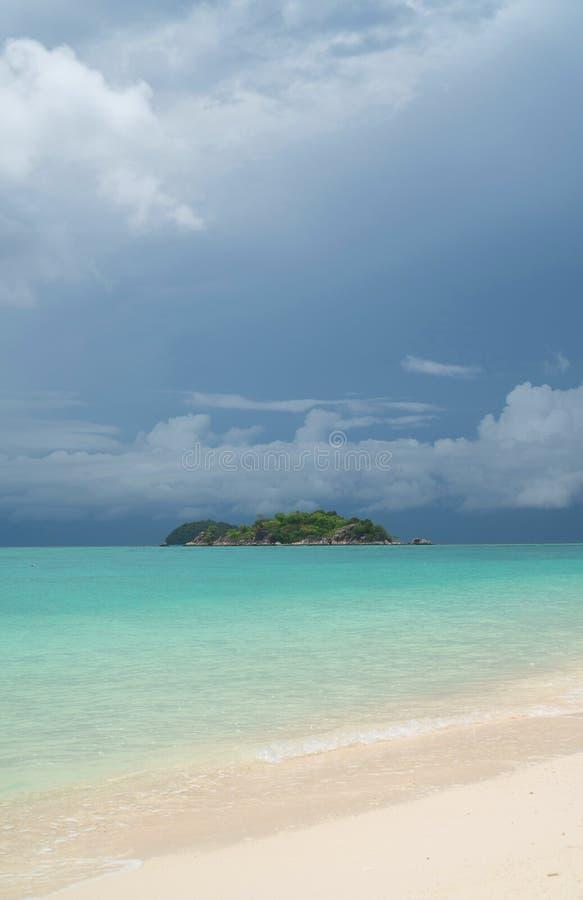 Παραλία και θάλασσα με το μικρό νησί πέρα από το νεφελώδη ουρανό στοκ εικόνα με δικαίωμα ελεύθερης χρήσης