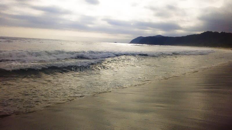 Παραλία με τα κύματα και το χρυσό φως στοκ εικόνες