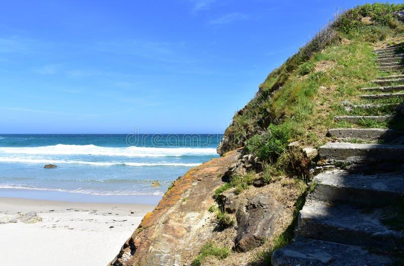 Παραλία με τον απότομο βράχο, την άσπρη άμμο, τα κύματα και τα σκαλοπάτια Μπλε ουρανός, ηλιόλουστη ημέρα, Lugo, Ισπανία στοκ εικόνα με δικαίωμα ελεύθερης χρήσης