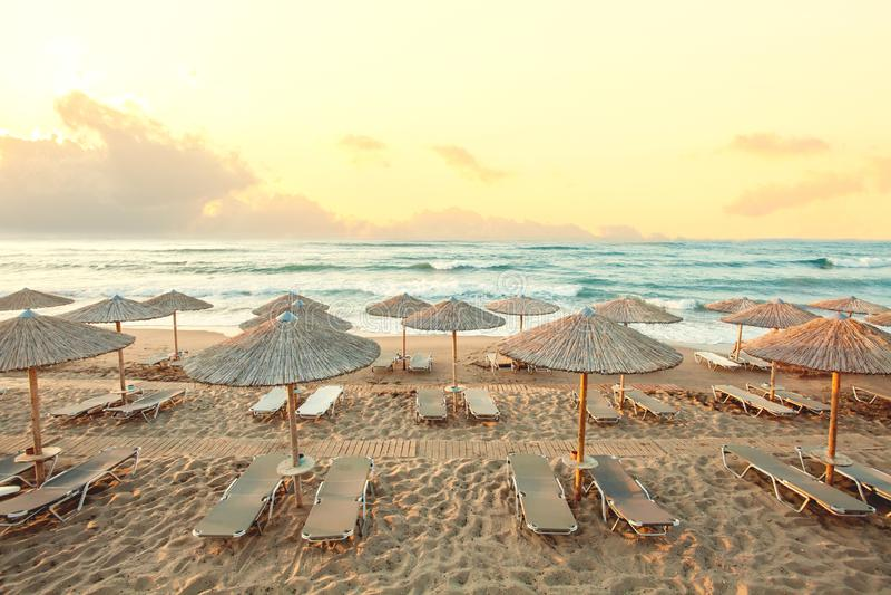 Παραλία πρωινού, ομπρέλες, sunbeds και ουρανός αυγής θερινό παιχνίδι διαβατηρίων διακοπών έννοιας παραλιών βρετανικό στοκ εικόνες με δικαίωμα ελεύθερης χρήσης