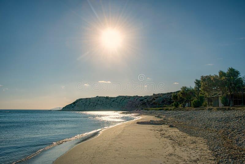 Παραλία χαλικιών που καλύπτεται μερικώς με την άμμο από το ηλιοβασίλε στοκ εικόνες