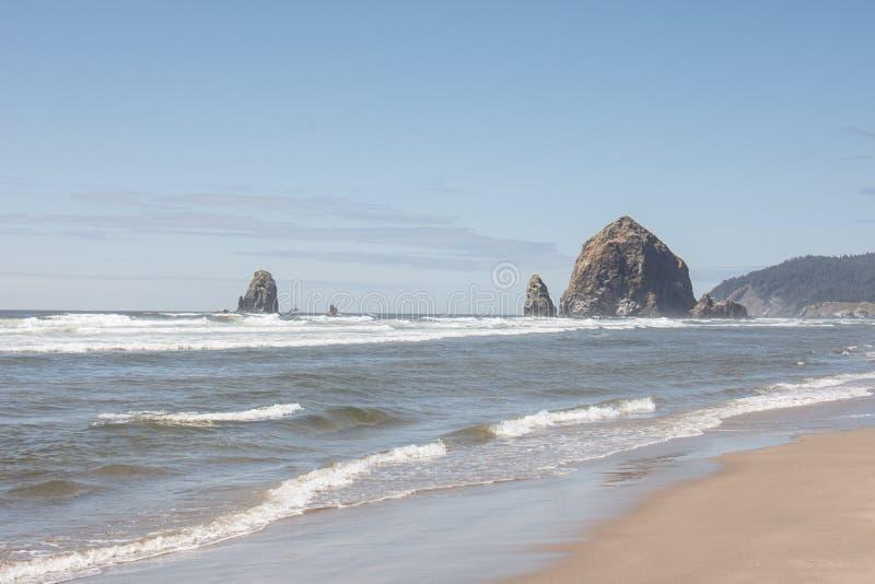 Παραλία Όρεγκον πυροβόλων με μια άποψη του διάσημου βράχου θυμωνιών χόρτου στοκ εικόνες με δικαίωμα ελεύθερης χρήσης