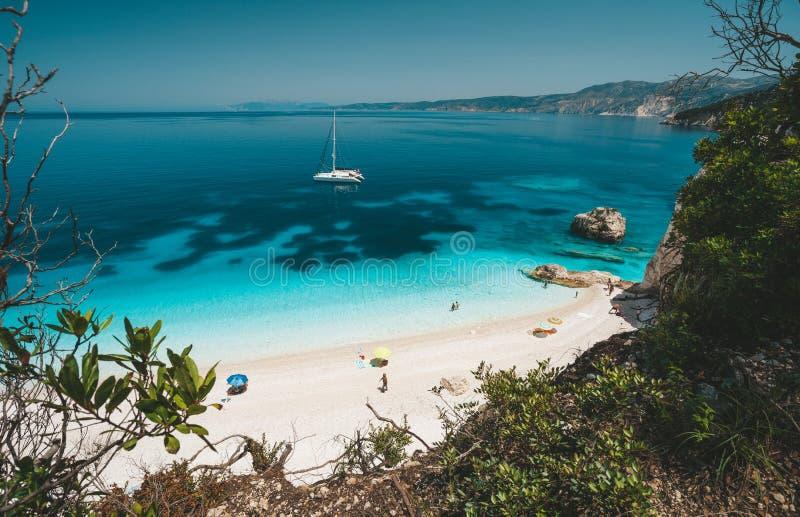 Παραλία Fteri, Cephalonia Kefalonia, Ελλάδα Άσπρο γιοτ καταμαράν στο σαφές μπλε θαλάσσιο νερό Τουρίστες στην αμμώδη παραλία πλησί στοκ φωτογραφία