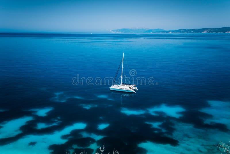 Παραλία Kefalonia, Ελλάδα Fteri Άσπρο γιοτ καταμαράν στη σαφή μπλε διαφανή θάλασσα με τη σκοτεινή επιφάνεια νερού σχεδίων στοκ φωτογραφία με δικαίωμα ελεύθερης χρήσης