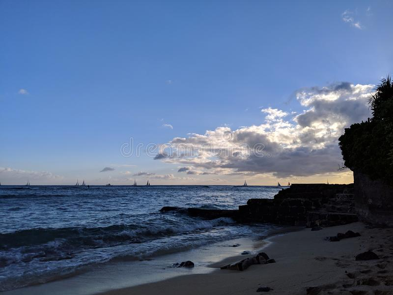 Παραλία Makalei με τα κύματα που περιτυλίγουν, τον τοίχο βράχου λάβας και τις βάρκες στο νερό στο σούρουπο στοκ εικόνες με δικαίωμα ελεύθερης χρήσης