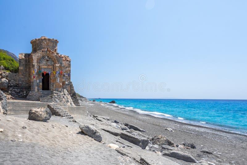 Παραλία Pavlos επιβαρύνσεων με την εκκλησία του Saint-Paul, μια πολύ παλαιά βυζαντινή εκκλησία που χτίστηκε στη θέση Selouda στοκ εικόνες