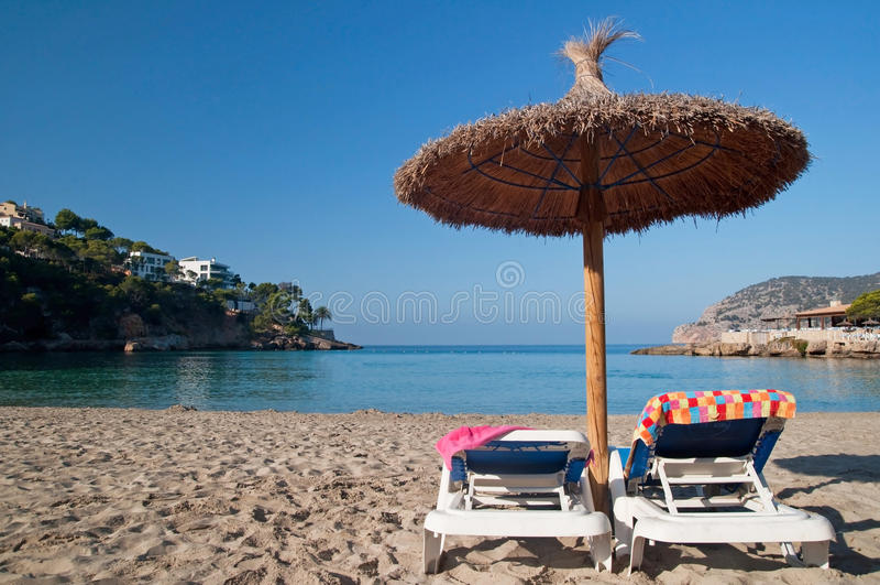 Παραλία sunbeds με τις πετσέτες και την ομπρέλα στοκ εικόνα με δικαίωμα ελεύθερης χρήσης