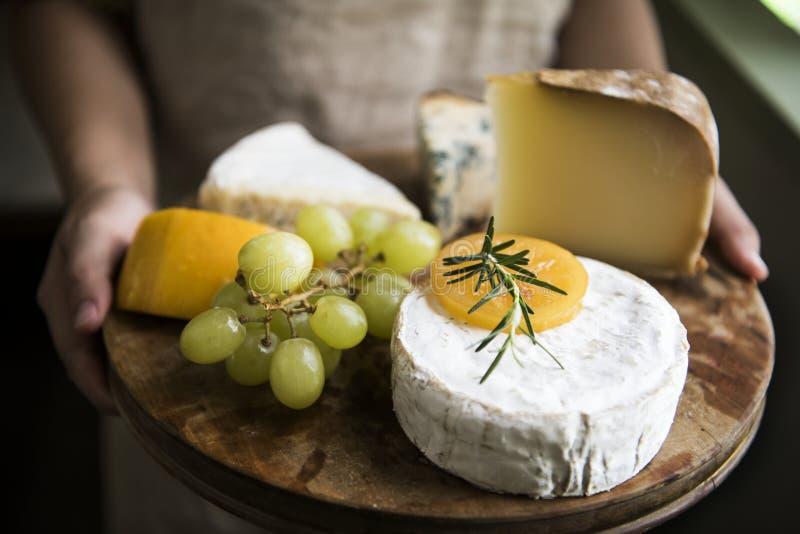 Παραλλαγή του τυριού και των πράσινων σταφυλιών σε μια ξύλινη ιδέα συνταγής φωτογραφίας τροφίμων πιατελών στοκ φωτογραφία με δικαίωμα ελεύθερης χρήσης