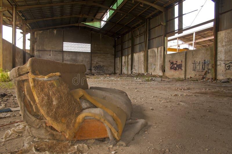 Παραμένει ενός καναπέ σε μια εγκαταλειμμένη βιομηχανική αποθήκη εμπορευμάτων στοκ εικόνα