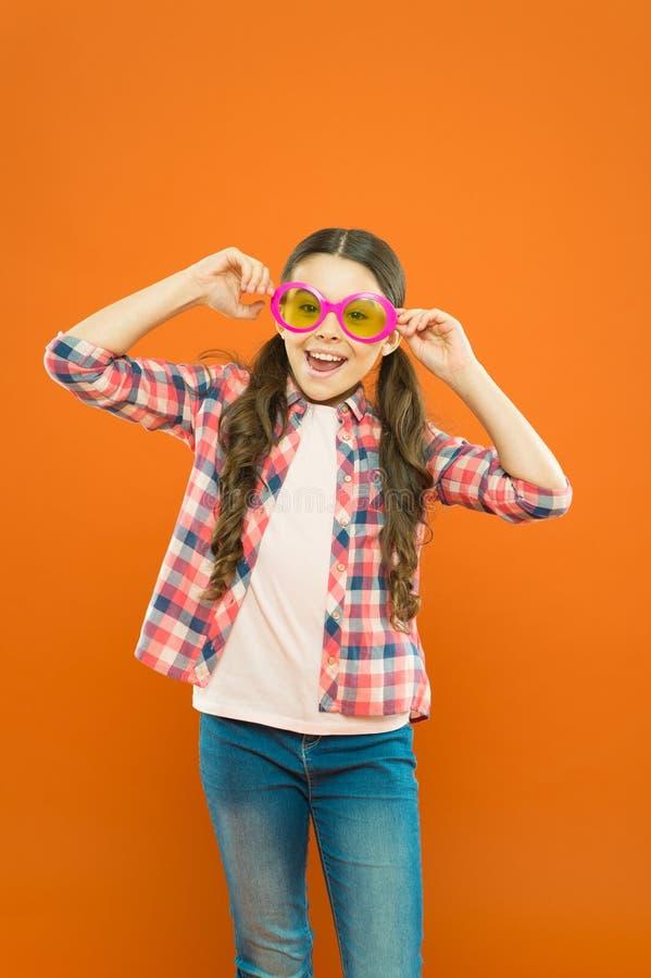 Παραμονή με τα γυαλιά Μικρό παιδί που χαμογελά με τα φανταχτερά γυαλιά κομμάτων στο πορτοκαλί υπόβαθρο Αστείο κορίτσι που φορά το στοκ φωτογραφία με δικαίωμα ελεύθερης χρήσης