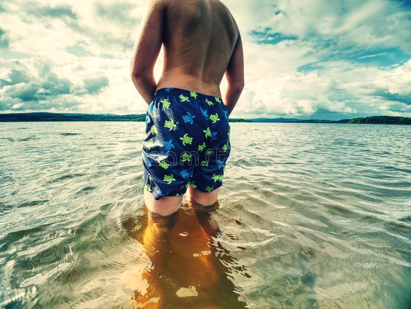 Παραμονή παιδιών στο κρύο κρύο νερό δοκιμής μυρμηγκιών λιμνών άνοιξη στον ηλιόλουστο καιρό στοκ εικόνα με δικαίωμα ελεύθερης χρήσης