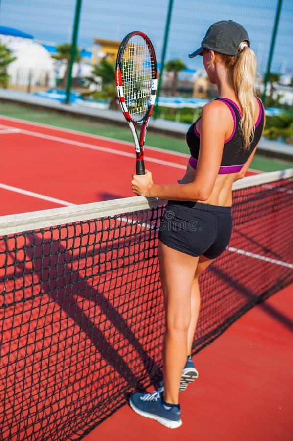 Παραμονή ρακετών εκμετάλλευσης γυναικών πίσω στο γήπεδο αντισφαίρισης στοκ φωτογραφία με δικαίωμα ελεύθερης χρήσης