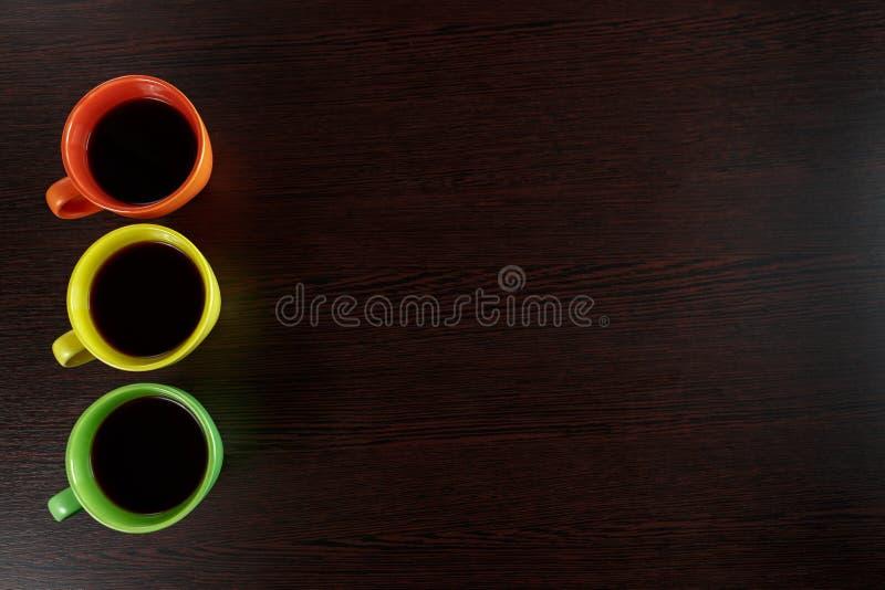 Παραμονή τριών φλυτζανιών καφέ στο σκοτεινό καφετή ξύλινο πίνακα όπως τα φω'τα στοκ εικόνα με δικαίωμα ελεύθερης χρήσης