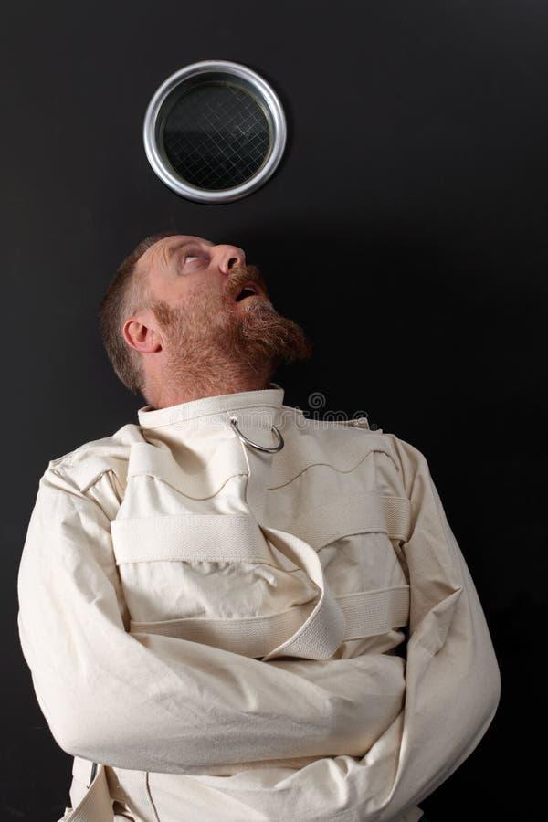 Παρανοϊκό άτομο σε έναν περισταλτικό μανδύα στοκ εικόνες