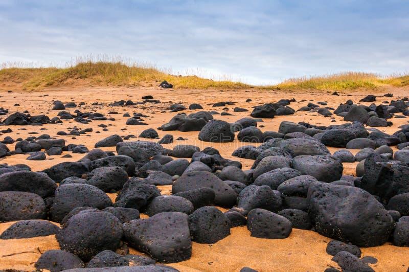 Παραλία άμμου με τους μαύρους βράχους στην Ισλανδία - μικρή πόλη στη χερσόνησο Snaefellsnes στοκ εικόνες