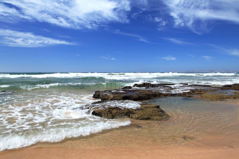 Παραλία κοντά σε Mosselbay Νότια Αφρική κατά τη διάρκεια της ηλιοφάνειας πρωινού κάτω από έναν νεφελώδη ουρανό στοκ εικόνα