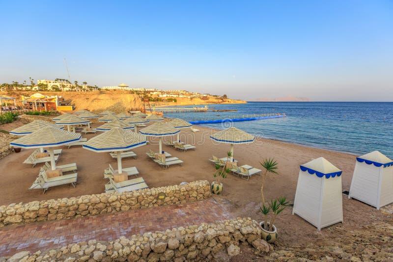 Παραλία με τις καρέκλες γεφυρών και parasol κατά τη διάρκεια του ηλιοβασιλέματος στοκ φωτογραφίες με δικαίωμα ελεύθερης χρήσης
