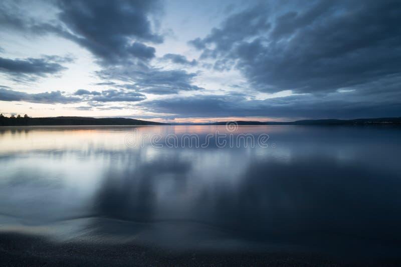 Παραλία της ήρεμης σουηδικής λίμνης που φωτογραφίζεται στο λυκόφως στοκ εικόνες