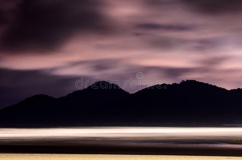 Παραλία τη νύχτα με την άμμο, τα κύματα θάλασσας και τα βουνά στοκ εικόνα με δικαίωμα ελεύθερης χρήσης