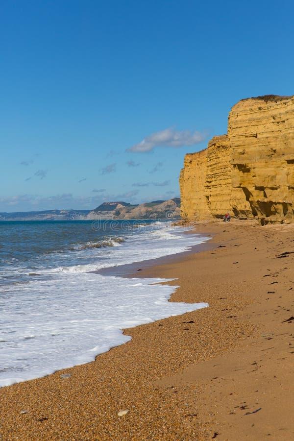 Παραλία Dorset Burton Bradstock βρετανικών ιουρασική ακτών με τους απότομους βράχους ψαμμίτη και τα άσπρα κύματα το καλοκαίρι με  στοκ φωτογραφία με δικαίωμα ελεύθερης χρήσης