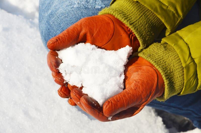 Παραδίδει τα γάντια κρατά το χιόνι στοκ φωτογραφία