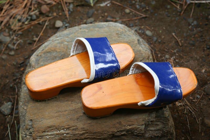 Παραδοσιακά ιαπωνικά ξύλινα παπούτσια της Zen σε έναν βράχο σε έναν κήπο στοκ φωτογραφία με δικαίωμα ελεύθερης χρήσης
