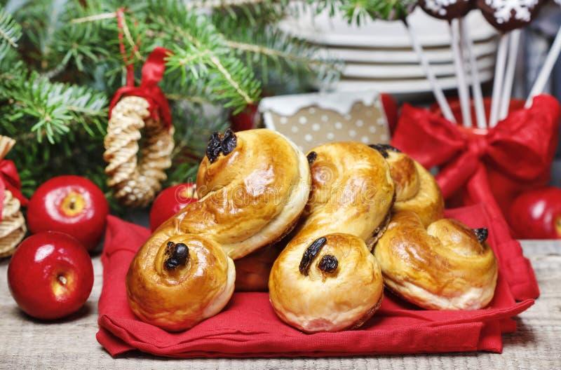 Παραδοσιακά σουηδικά κουλούρια στη ρύθμιση Χριστουγέννων Ένα κουλούρι σαφρανιού, στοκ εικόνες