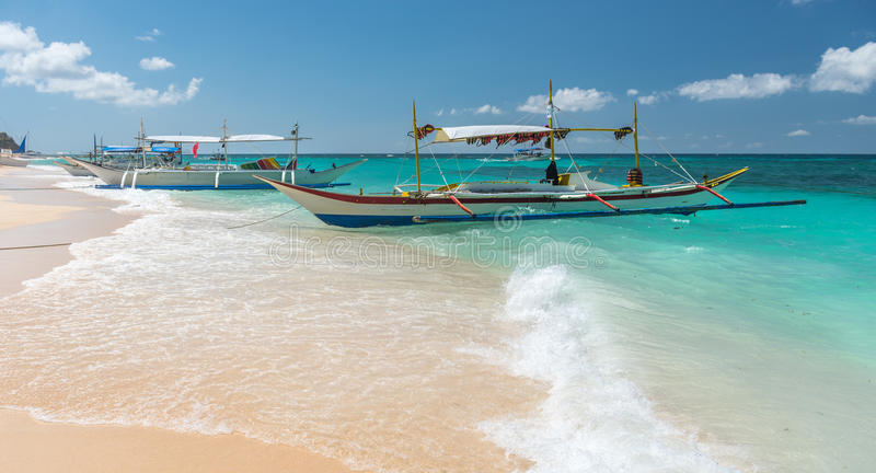 Παραδοσιακές των Φηληππίνων ασιατικές βάρκες γύρου ταξί πορθμείων στην παραλία puka στοκ εικόνες