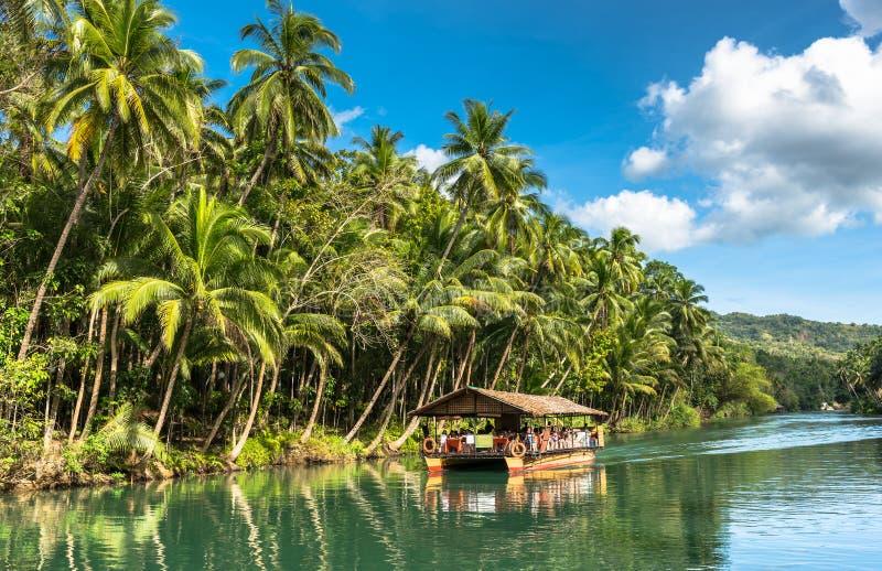 Παραδοσιακή βάρκα συνόλων με τους τουρίστες σε έναν πράσινο ποταμό ζουγκλών στοκ φωτογραφία με δικαίωμα ελεύθερης χρήσης