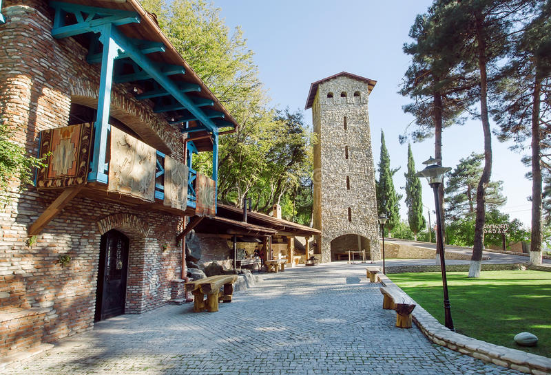 Παραδοσιακή της Γεωργίας αρχιτεκτονική με τον πύργο τούβλου, το αγροτικά σπίτι και το πάρκο στοκ εικόνα με δικαίωμα ελεύθερης χρήσης