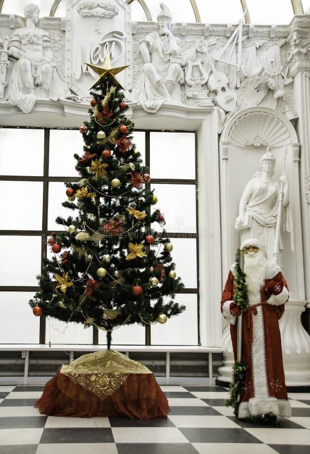 Παραδοσιακός Άγιος Βασίλης που στέκεται κοντά στο χριστουγεννιάτικο δέντρο που ντύνεται επάνω για μια καλή χρονιά και Χριστούγενν στοκ φωτογραφίες