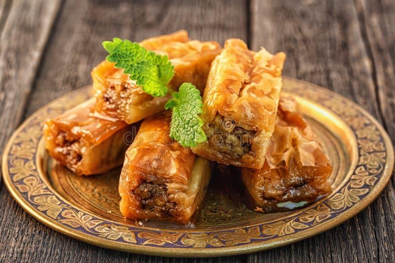 Παραδοσιακό αραβικό επιδόρπιο Baklava με το μέλι και τα ξύλα καρυδιάς στοκ εικόνες