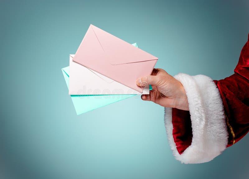 Παραδώστε το κοστούμι Άγιος Βασίλης κρατά τους φακέλους στοκ εικόνες