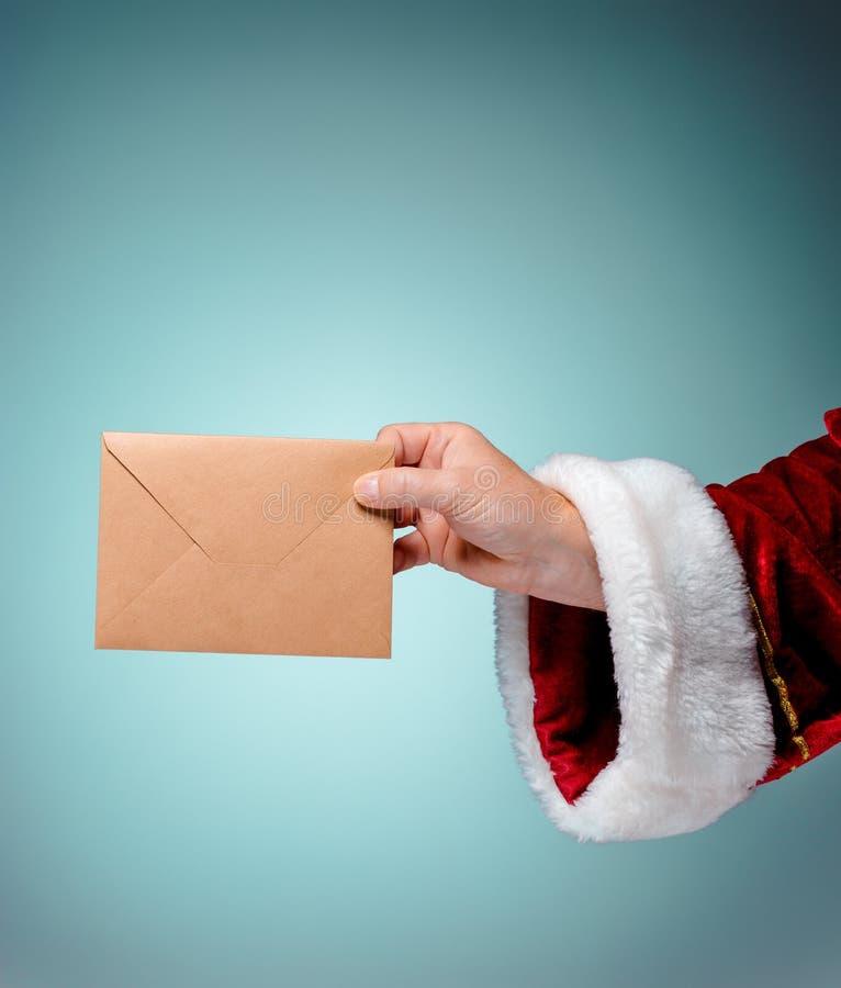 Παραδώστε το κοστούμι Άγιος Βασίλης κρατά το φάκελο στοκ φωτογραφία με δικαίωμα ελεύθερης χρήσης