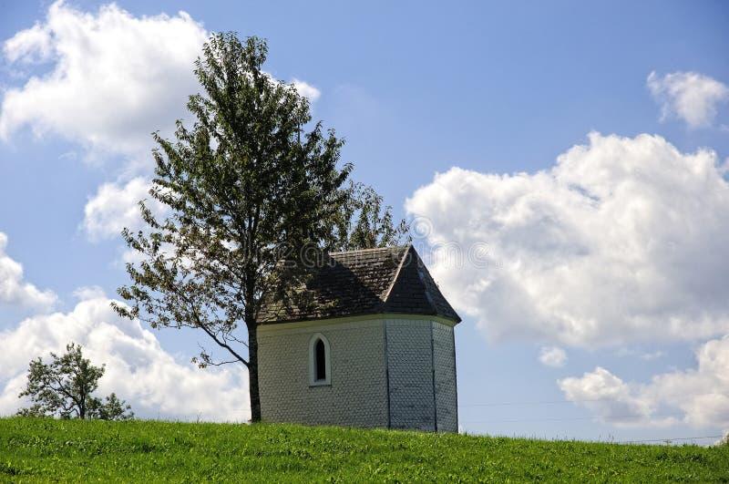 Παρεκκλήσι στο πράσινο πεδίο με γαλάζιο ουρανό στοκ φωτογραφία