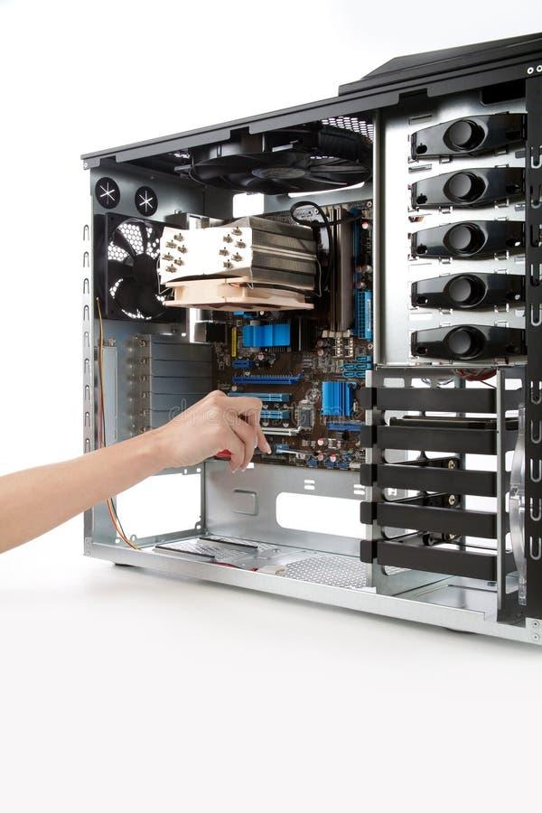 Παρεμβάλλοντας τη μητρική κάρτα μέσα στην περίπτωση υπολογιστών στοκ εικόνα