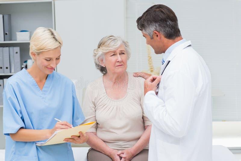 Παρηγορώντας ασθενής γιατρών ενώ το γράψιμο νοσοκόμων υποβάλλει έκθεση στοκ φωτογραφίες