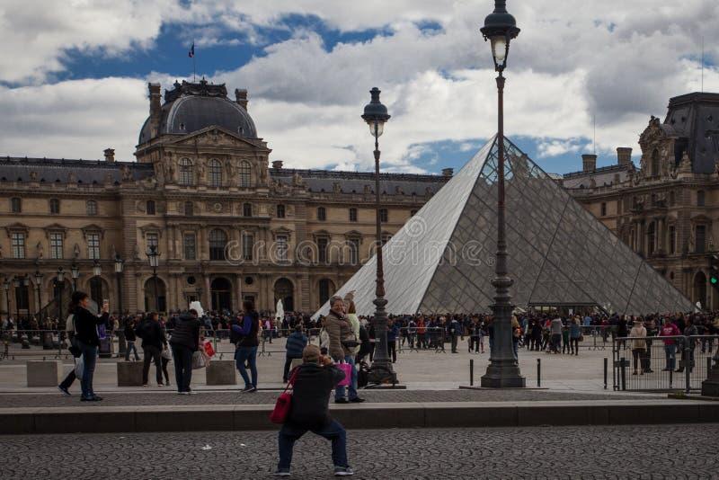 ΠΑΡΙΣΙ, ΓΑΛΛΙΑ - 30 ΣΕΠΤΕΜΒΡΊΟΥ 2016: τουρίστες μπροστά από το παλάτι του Λούβρου και την πυραμίδα του Λούβρου Το μουσείο του Λού στοκ εικόνες με δικαίωμα ελεύθερης χρήσης