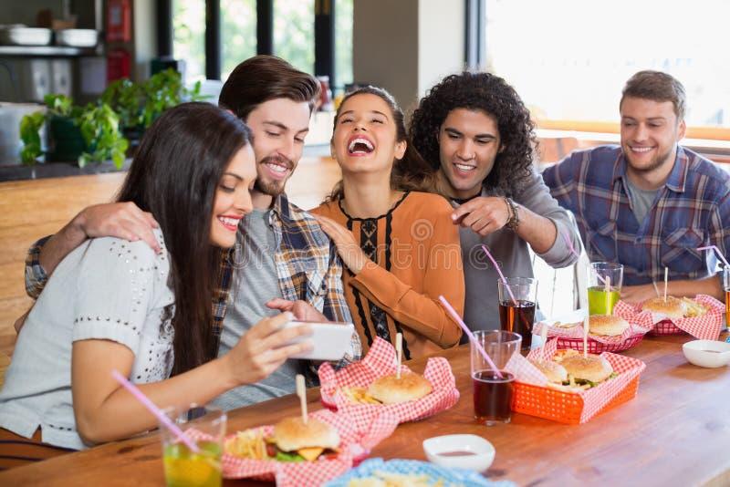 Παρουσίαση γυναικών κινητή στους εύθυμους φίλους στο εστιατόριο στοκ φωτογραφία με δικαίωμα ελεύθερης χρήσης