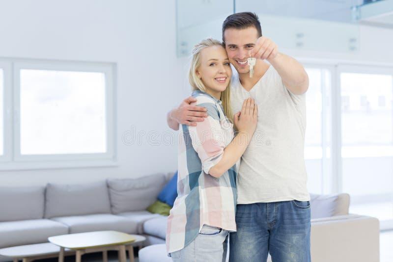 Παρουσίαση ζεύγους κλειδιά του καινούργιου σπιτιού τους στοκ εικόνα