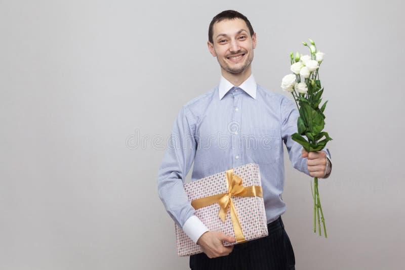 Παρουσιάζει για τα γενέθλια Γοητεία του ρομαντικού νεαρού άνδρα ευχαρίστησης στην μπλε ανθοδέσμη εκμετάλλευσης πουκάμισων των άσπ στοκ εικόνες