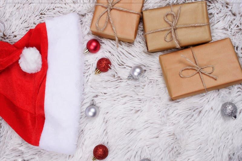 Παρουσιάζει, μπιχλιμπίδια Χριστουγέννων και καπέλο Santa στη γούνα στοκ φωτογραφίες