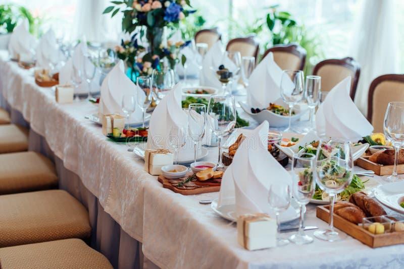 Παρουσιάστε την τιμή τών παραμέτρων Πίνακας που εξυπηρετείται για το γαμήλιο συμπόσιο, στενή επάνω άποψη Άσπρη πετσέτα σε ένα άσπ στοκ εικόνα