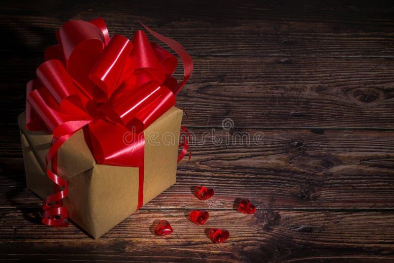Παρόν κιβώτιο με την κόκκινη κορδέλλα τόξων και shinny μικρές καρδιές για την ημέρα βαλεντίνων στοκ εικόνες