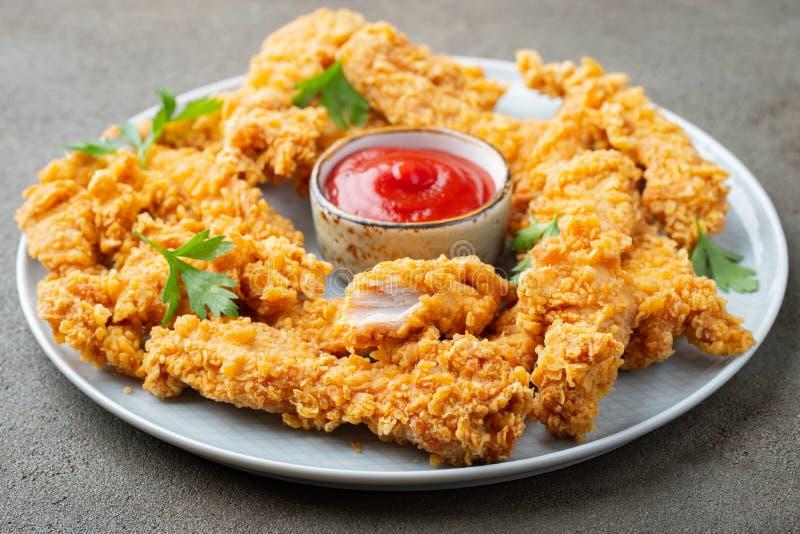 Πασπαλισμένες με ψίχουλα λουρίδες κοτόπουλου με το κέτσαπ ντοματών σε ένα άσπρο πιάτο Γρήγορο φαγητό στο σκοτεινό καφετί υπόβαθρο στοκ φωτογραφία με δικαίωμα ελεύθερης χρήσης