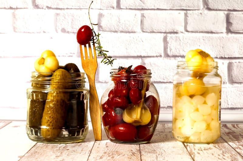 Παστωμένα αγγούρια, μικρές ντομάτες με το σκόρδο και το κρεμμύδι στο βάζο γυαλιού Ζυμωνομμένα τρόφιμα closeup στοκ φωτογραφία