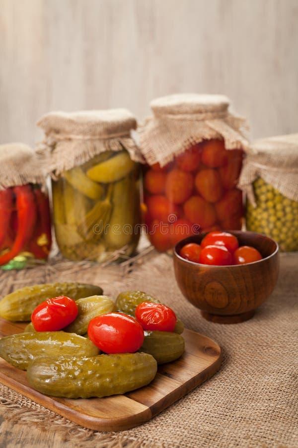 Παστωμένα συντηρημένα λαχανικά στα βάζα, τα αγγούρια, το πιπέρι, τις ντομάτες και τα μπιζέλια στοκ εικόνα με δικαίωμα ελεύθερης χρήσης