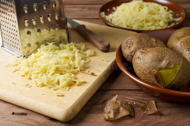 Πατάτα και ξυμένος την πατάτα σε έναν τέμνοντα πίνακα στοκ φωτογραφία