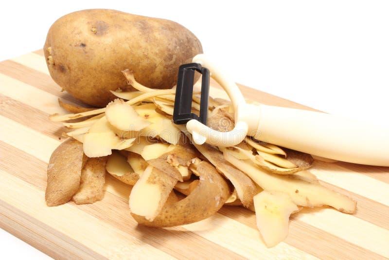 Πατάτα με τις φλούδες και peeler που βρίσκεται στον ξύλινο τέμνοντα πίνακα στοκ εικόνα