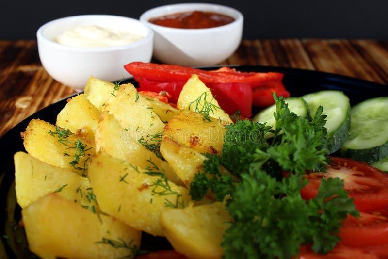 Πατάτα που ψήνεται σε έναν φούρνο με τα φρέσκα λαχανικά στοκ φωτογραφία